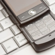 Abstract Cell Phone on Laptop Macro Image. - Stock Photo