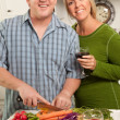 Happy Couple Preparing Food in Kitchen - Stock Photo