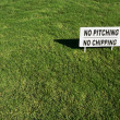 No Pitching or Chipping Sign on Lush Green Grass - Stock Photo