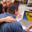 Couple In Kitchen Using Laptop with Yellow Oops Sign on Screen - Stockfoto