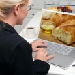 Woman In Kitchen Using Laptop Computer with Bread and Olive Oil on Screen — Stock Photo #2357143