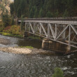 Iron Train Bridge Over Mountain River - Stock Photo