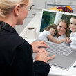 Woman In Kitchen Using Laptop with Woman and Children on Screen — Stock Photo #2357246