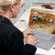 Woman In Kitchen Using Laptop with Kitchen Interior on Screen — Stock Photo #2357253