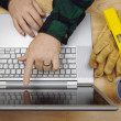Contractor Reviews Project on Laptop - Stock Photo