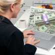 Woman In Kitchen Using Laptop with Stacks of Money on Screen - Stock Photo