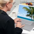 Woman In Kitchen Using Laptop to Research Travel with Palm Trees on Screen — Stock Photo #2357438