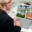Stock Photo: WomIn Kitchen Using Laptop to Research Real Estate