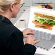 Girl Using Laptop, Sandwich on Screen — Stock Photo #2357601
