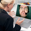 Girl Using Laptop with Man on Screen — Stock Photo