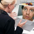 Stock Photo: Shocked Woman In Kitchen Using Laptop with Strange Man on Screen