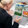 Stock Photo: Excited Woman In Kitchen Using Laptop to Sell or Buy a Home