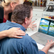 Couple In Kitchen Using Laptop to Research Travel — Stockfoto