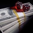 Stacks of Money and Red Dice on Black - Stock Photo