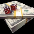 Stacks of Money and Red Dice on Black — Stock Photo