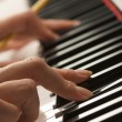 Woman Playing Digital Piano with Pencil - Stock Photo