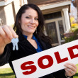 Stock Photo: Woman Holding Sold Sign and Keys