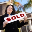 Woman Holding Sold Sign In Front of Home — Stock Photo #2358459