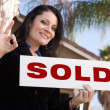 House and Woman Holding Sold Sign - Stock Photo