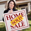 House and Woman Holding Sold Home Sign - Stock Photo