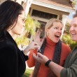 Real Estate Agent Handing keys to Couple - Stock Photo