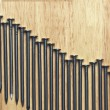Stock Photo: Declining Graph of Nails on Wood