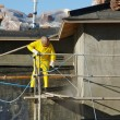 Construction Worker Pressure Washes House - Stockfoto