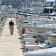 Man Walking the Dock Surrounded by Boats - Stock Photo