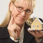 Thinking Woman Holding Model House — Stock Photo