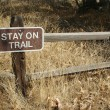 Stay on Trail Sign on Wooden Fence - Stock Photo