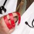 Doctor with Stethoscope Holding Red Measuring Tape - Stock Photo