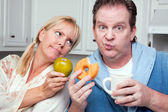 Couple in Kitchen with Fruit and Donuts — Photo