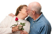 Kissing Senior Couple with Red Rose — Stock Photo