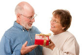 Happy Senior Couple Exchanging Gift Isolated on White — Stock Photo