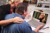 Par med laptop med kvinna på skärmen — Stockfoto