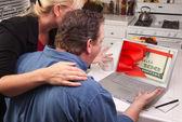 Couple à l'aide d'ordinateur portable avec de l'argent sur l'écran — Photo