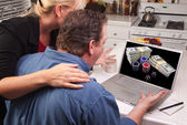 Couple Using Laptop with Money on Screen — Stock Photo