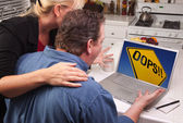 Couple In Kitchen Using Laptop with Yellow Oops Sign on Screen — Stock Photo