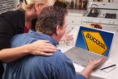 Par i köket med laptop med gula framgång logga på skärmen — Stockfoto