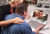Couple In Kitchen Using Laptop Computer with Hands Playing Piano on Screen — Stock Photo