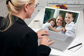 Woman In Kitchen Using Laptop with Woman and Children on Screen — Stock Photo