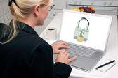 Mulher na cozinha usando laptop com cadeados na tela — Foto Stock