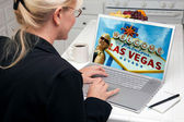Woman In Kitchen Using Laptop with Las Vegas Sign on Screen — Stock fotografie
