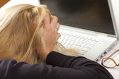 Frustrated Female Holding Head in Hands Using Laptop Computer — Stock Photo