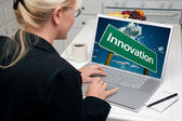Woman In Kitchen Using Laptop with Innovation Road Sign on Screen — Stock Photo
