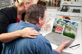 Couple In Kitchen Using Laptop to Research Real Estate — Stock Photo
