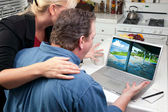 Couple In Kitchen Using Laptop to Research Travel — Stock Photo