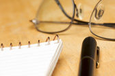 Pen, Pad and Glasses on Wood Background — Stock Photo