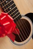 Gitar ve yaylı kırmızı kurdele ile — Stok fotoğraf