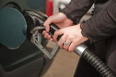 Woman's Hands Pumping Gasoline at the Service Station — Stock Photo
